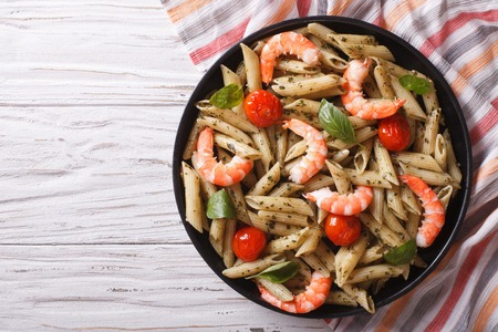 shrimp: pasta with shrimp, tomato and pesto sauce on a plate.horizontal top view Stock Photo