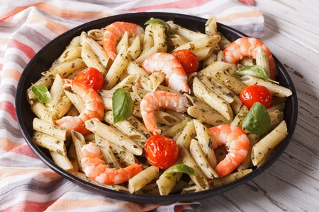 tomato: penne pasta with shrimps, tomato and pesto closeup on a plate. horizontal Stock Photo