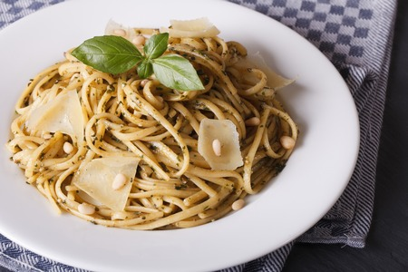 linguine pasta: linguine pasta with pesto sauce, pine nuts and Parmesan cheese close-up on a white plate. horizontal