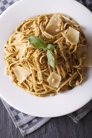 linguine pasta: linguine pasta with pesto, pine nuts and parmesan close-up on a white plate. Vertical top view Stock Photo
