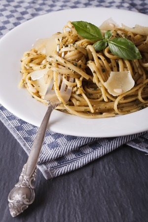 linguine pasta: linguine pasta with pesto, pine nuts and parmesan close-up on a white plate. vertical Stock Photo