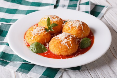 recipe background: Delicious fried arancini rice balls with tomato sauce on the table. horizontal Stock Photo