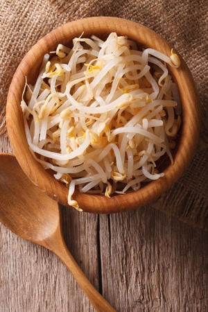 beansprouts: Raw sprouts of mung beans in a wooden bowl on the table. vertical top view Stock Photo