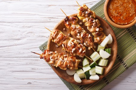singapore culture: Chicken satay with a delicious peanut sauce and fresh salad on the plate. horizontal top view Stock Photo