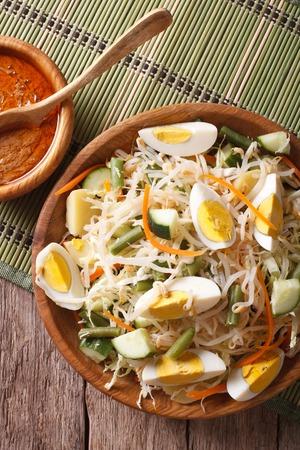gado: Gado Gado salad with peanut sauce close-up on the table. vertical top view