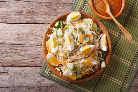 Gado Gado Indonesian salad with peanut sauce on the table. horizontal top view Stock Photo