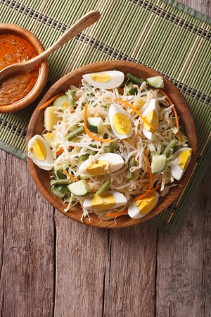 Gado Gado Indonesian salad with peanut sauce on the table. vertical top view