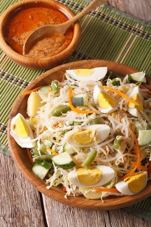 gado: Gado Gado Indonesian vegetable salad close-up on the table. Vertical