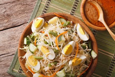 gado: Traditional Indonesian salad gado-gado with peanut sauce close-up on the table. Horizontal top view above Stock Photo