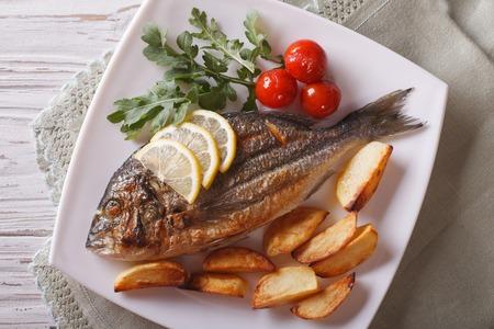 dorado fish: Grilled dorado fish with fried potatoes, lemon and tomato close-up on a plate. horizontal top view