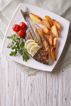dorado fish: Grilled dorado fish with fried potatoes, lemon and tomato close-up on a plate. Vertical top view Stock Photo