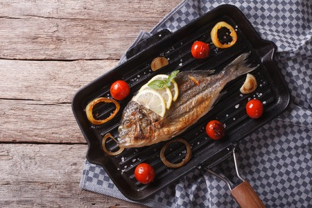 Dorado fish cooking on the black grill pan. horizontal view from above Reklamní fotografie
