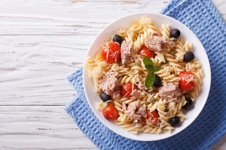 fusilli pasta met tonijn, tomaten en Parmezaanse kaas op tafel. horizontale bovenaanzicht