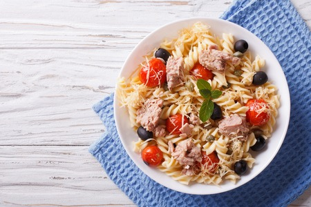 tomato: fusilli pasta with tuna, tomatoes and parmesan on the table. horizontal top view