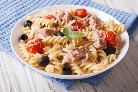 fusilli pasta met tonijn, parmezaanse kaas en tomaten in een kom. Horizontaal