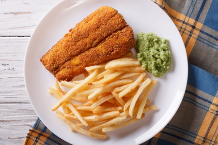 english food: English food: fried fish in batter with chips and pea puree close-up on a plate. horizontal view from above