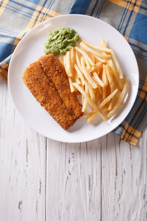 english food: English food: fried fish in batter with chips and pea puree on a plate. vertical top view
