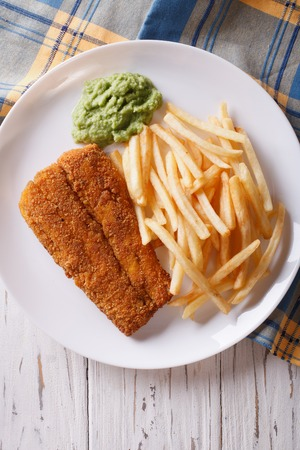 english food: English food: fried fish in batter with chips and pea puree close-up on a plate. vertical top view