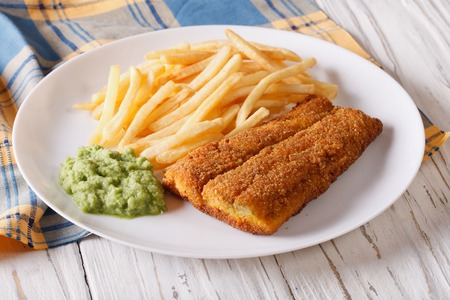 english food: English food: fish in breadcrumbs with fried potatoes and pea puree on a plate. horizontal