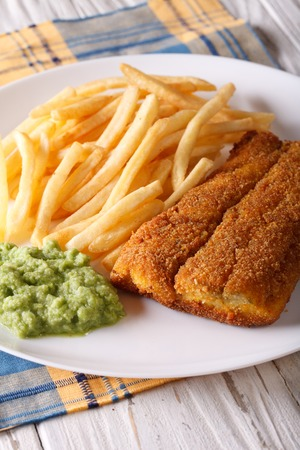 comida inglesa: Ingl�s alimentos: fr�e los filetes de pescado y patatas fritas y pur� de guisantes de cerca en un plato. Vertical