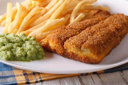 comida inglesa: Ingl�s alimentos: fr�e los filetes de pescado y patatas fritas y pur� de guisantes de cerca en un plato. horizontal