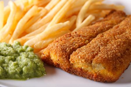 comida inglesa: Ingl�s alimentos: fr�e los filetes de pescado y patatas fritas y pur� de guisantes macro. horizontal Foto de archivo