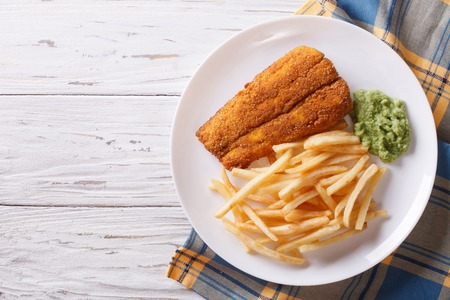 English food: fried fish in batter with chips and pea puree on a plate. horizontal view from above