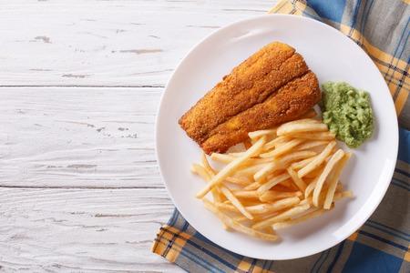 comida inglesa: Inglés alimentos: pescado frito rebozado con patatas fritas y puré de guisantes en un plato. visión horizontal desde arriba Foto de archivo