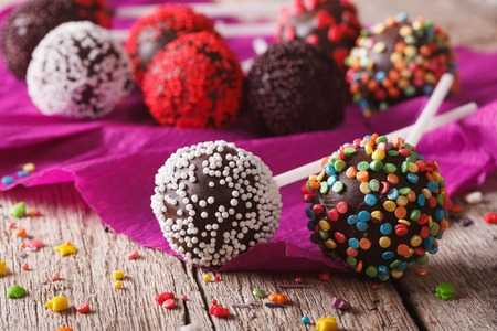 eating cake: Festive chocolate cake pops with candy sprinkles close-up on the table. horizontal