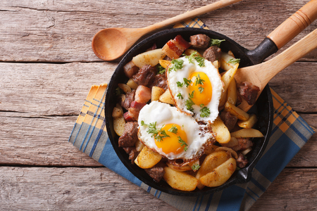 tyrolean: Tyrolean fried potatoes with meat, bacon and eggs in a pan. horizontal top view