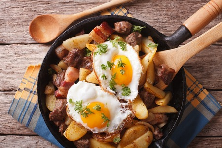 tyrolean: Tyrolean fried potatoes with meat, bacon and eggs in a pan close-up. horizontal top view Stock Photo