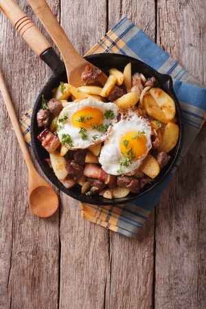 tyrolean: Tyrolean fried potatoes with meat, bacon and eggs in a pan. vertical top view