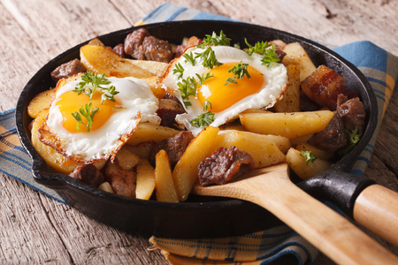 european cuisine: European cuisine: fried potatoes with meat, bacon and eggs in a pan close-up. horizontal