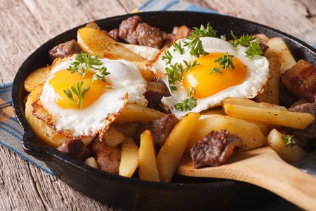 human meat: Austrian food: fried potatoes with meat, ham and eggs in a pan close-up. horizontal