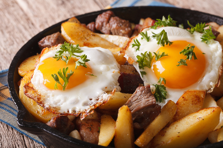 eggs and bacon: Tyrolean food: fried potatoes with meat, ham and eggs in a pan close-up. horizontal