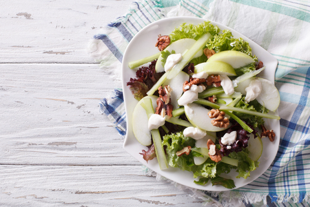 fruit salad: Waldorf Salad with apples, celery and walnuts on a plate. horizontal view from above Stock Photo
