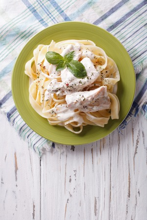 alfredo: alfredo pasta in cream sauce with chicken on a plate. vertical top view