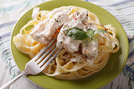 alfredo: fettuccini alfredo pasta with chicken closeup on a plate. horizontal
