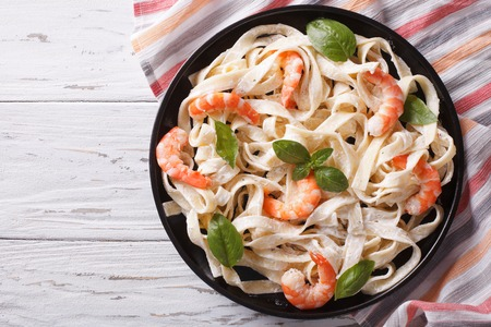 fettuccini pasta in cream sauce with shrimp on a plate on the table. horizontal view from above Stock Photo