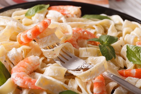 fettuccini Pasta mit Sahnesauce mit Garnelen Makro auf einer Platte. Horizontal