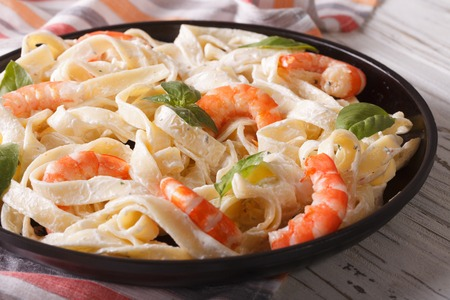 pasta sauce: Italian pasta fettuccine in a creamy sauce with shrimp close-up on a plate. horizontal