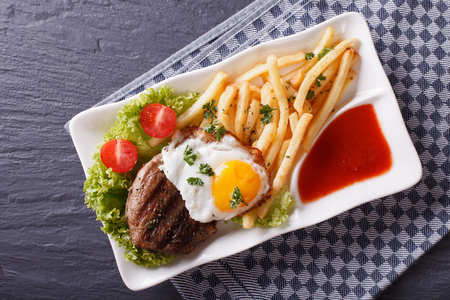 potato fries: Grilled beefsteak with fried egg and French fries served on a plate. horizontal view from above