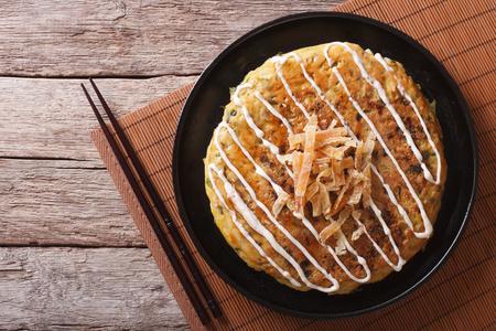 plato de comida: Okonomiyaki japonesa en una mesa y palillos. vista superior horizontal Foto de archivo