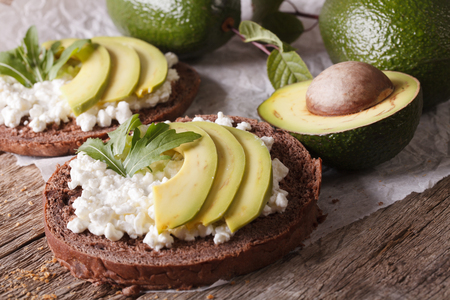 Simple sandwiches with avocado, cottage cheese and arugula close-up on the table. horizontal Фото со стока