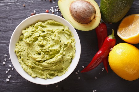 Mexican guacamole sauce with ingredients close-up on the table. horizontal view from above