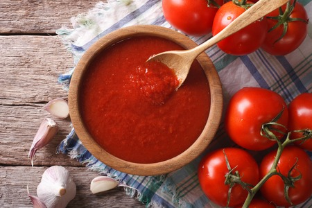 tomato sauce with garlic and basil in a wooden bowl closeup. horizontal view from above
