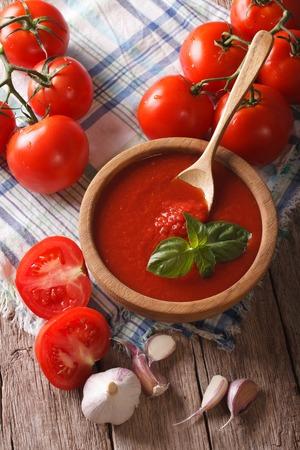 salsa de tomate con ajo y albahaca en un primer plano de madera. vertical Foto de archivo