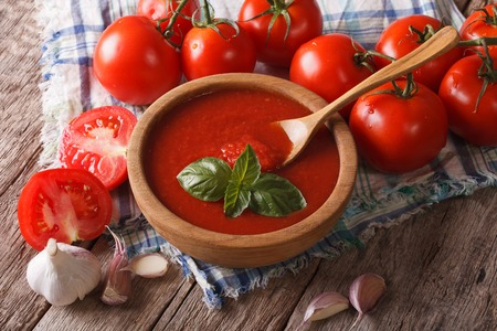 Homemade red tomato sauce with garlic and basil in a wooden bowl closeup. horizontal