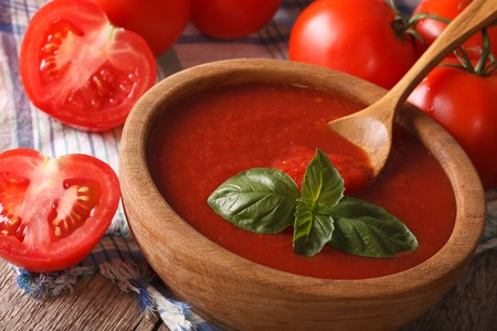 Fresh red tomato sauce with basil in a wooden bowl closeup. Horizontal
