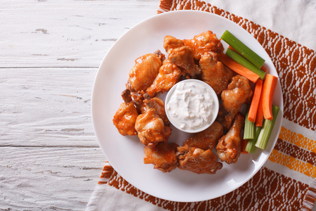 chicken wings: buffalo chicken wings with cheese sauce and celery on the table. horizontal view from above